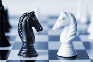Head to head - knights on a chess board, in blue duotone.  Shall